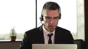 Homem de negócios que usa auriculares para falar no telefone video estoque