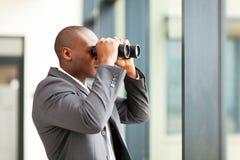 Homem de negócios que usa binóculos fotografia de stock