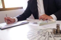 Homem de negócios que usa a calculadora com dinheiro e pilha de moedas na mesa imagens de stock