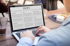 Homem de negócios que usa o artigo noticioso da leitura do portátil no portátil/tela de computador imagem de stock royalty free