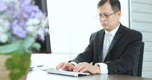 Homem de negócios que usa o computador para trabalhar no escritório video estoque