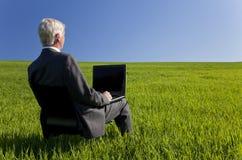 Homem de negócios que usa o computador portátil em Fie verde Fotografia de Stock Royalty Free