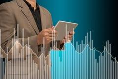 Homem de negócios que usa o gráfico virtual do controle da tabuleta na tela fotos de stock royalty free