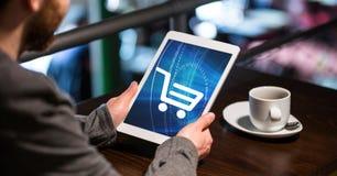 Homem de negócios que usa o PC da tabuleta com ícone do carrinho de compras na tela fotografia de stock royalty free
