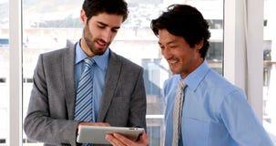 Homem de negócios que usa o PC da tabuleta com seu colega video estoque