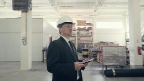 Homem de negócios que usa o PC da tabuleta na usina filme