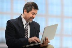 Homem de negócios que usa o portátil Fotografia de Stock Royalty Free