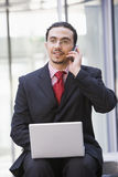 Homem de negócios que usa o portátil e o telefone móvel fora Fotografia de Stock