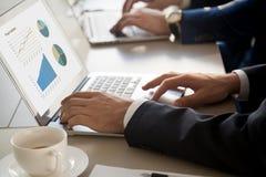 Homem de negócios que usa o portátil, estatísticas na tela, fim do projeto acima Fotografia de Stock