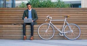 Homem de negócios que usa o portátil na rua 4k vídeos de arquivo