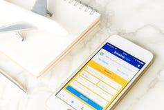 Homem de negócios que usa o registro COM para registrar sua viagem no smartphone fotos de stock