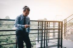 Homem de negócios que usa o smartphone antes de trabalhar na manhã fotografia de stock royalty free