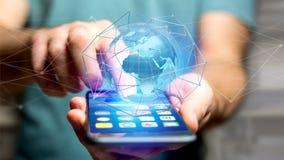 Homem de negócios que usa o smartphone com uma rede conectada sobre uma orelha Imagens de Stock
