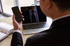 Homem de negócios que usa o smartphone e o portátil no escritório Foto de Stock