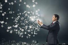 Homem de negócios que usa o smartphone Meios mistos Foto de Stock