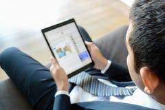 Homem de negócios que usa o tablet pc ao sentar-se no sofá Imagem de Stock