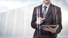 Homem de negócios que usa o tablet pc com a folha de prova do servidor de dados filme