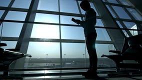 Homem de negócios que usa o tablet pc no aeroporto silhueta de um viajante do homem com trouxa Negócio e curso filme