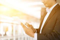 Homem de negócios que usa o tablet pc no estação de caminhos-de-ferro Fotografia de Stock Royalty Free