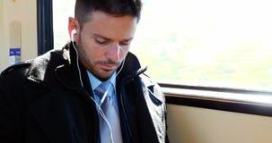 Homem de negócios que usa o telefone celular ao escutar a música filme