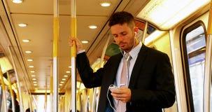 Homem de negócios que usa o telefone celular ao escutar a música vídeos de arquivo