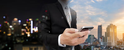 Homem de negócios que usa o telefone celular com arquitetura da cidade panorâmico da noite e do dia da cidade de Banguecoque fotos de stock