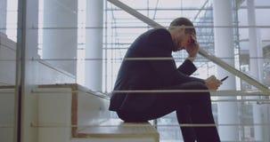 Homem de negócios que usa o telefone celular em escadas no escritório 4k vídeos de arquivo