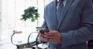 Homem de negócios que usa o telefone celular móvel ao mover-se em baixo na escada rolante i 4k vídeos de arquivo