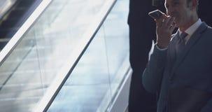 Homem de negócios que usa o telefone celular na escada rolante em um escritório moderno 4k video estoque