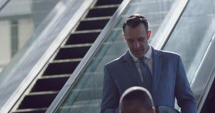 Homem de negócios que usa o telefone celular na escada rolante em um escritório moderno 4k vídeos de arquivo