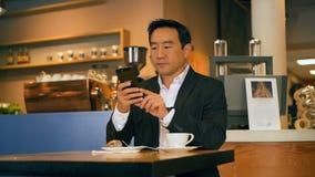 Homem de negócios que usa o telefone celular no café 4k video estoque