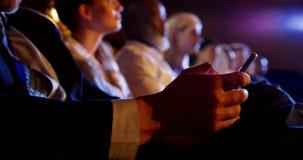 Homem de negócios que usa o telefone celular no seminário do negócio no auditório 4k filme