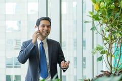 Homem de negócios que usa o telefone celular perto da janela do escritório em recepções Imagem de Stock
