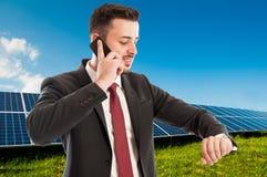 Homem de negócios que usa o telefone e verificando o tempo no campo fotovoltaico imagens de stock