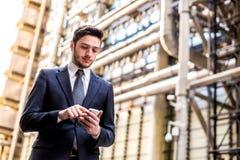Homem de negócios que usa o telefone esperto imagem de stock