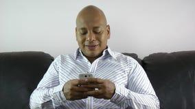 Homem de negócios que usa o telefone esperto que envia por correio eletrónico em casa video estoque