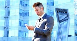 Homem de negócios que usa o telefone móvel video estoque