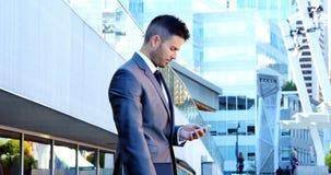 Homem de negócios que usa o telefone móvel filme