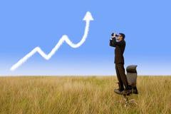 Homem de negócios que usa os binóculos que olham a nuvem do gráfico do crescimento Imagens de Stock Royalty Free