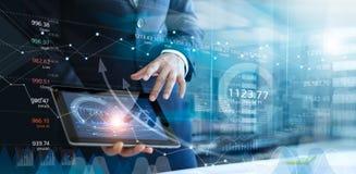 Homem de negócios que usa a tabuleta que analisa dados das vendas e gráfico do crescimento econômico imagem de stock royalty free