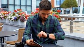Homem de negócios que usa a tabuleta digital ao comer o café video estoque