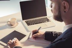Homem de negócios que usa a tabuleta digital e tomando notas ao sentar-se no local de trabalho Fotografia de Stock Royalty Free