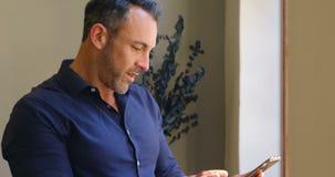 Homem de negócios que usa a tabuleta digital no escritório 4k video estoque
