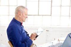 Homem de negócios que usa a tabuleta e o portátil digitais ao sentar-se na mesa de escritório e ao trabalhar no projeto novo foto de stock