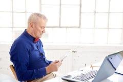 Homem de negócios que usa a tabuleta e o portátil digitais ao sentar-se na mesa de escritório e ao trabalhar no projeto novo fotografia de stock