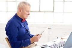 Homem de negócios que usa a tabuleta e o portátil digitais ao sentar-se na mesa de escritório e ao trabalhar no projeto novo imagens de stock