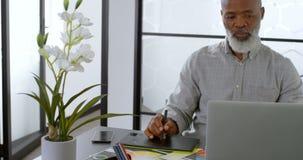 Homem de negócios que usa a tabuleta gráfica na mesa 4k video estoque