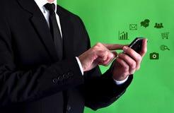 Homem de negócios que usa um smartphone com ícones virtuais Imagens de Stock Royalty Free