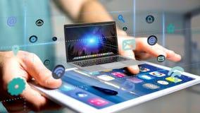 Homem de negócios que usa um smartphone com um computador que cerca pelo ap Fotografia de Stock Royalty Free