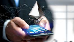 Homem de negócios que usa um smartphone com uma moeda cripto s de Ethereum Imagem de Stock